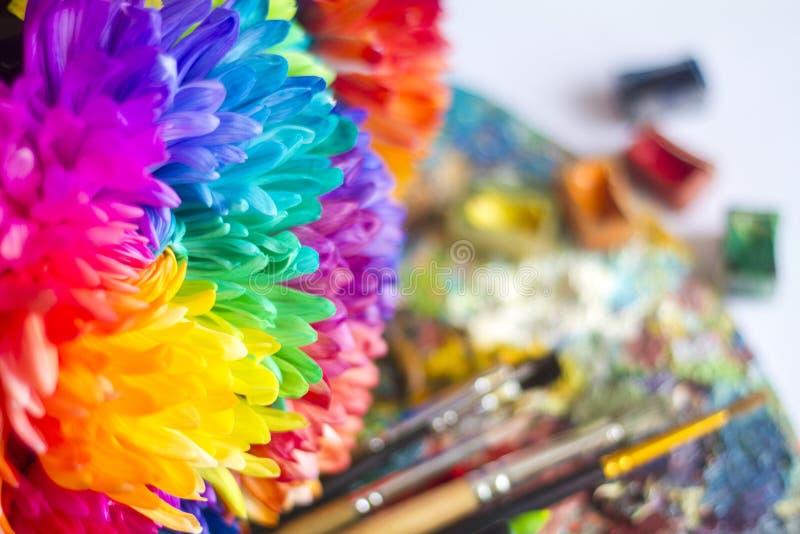 Mehrfarbige Chrysanthemen auf der Palette mit Farben und Bürsten des Künstlers lizenzfreie stockfotografie