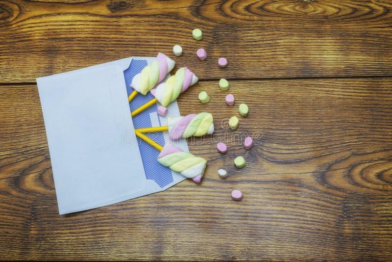 Mehrfarbige Eibische in einem Umschlag, Liebesmitteilung sendend Hölzerner Hintergrund lizenzfreies stockfoto