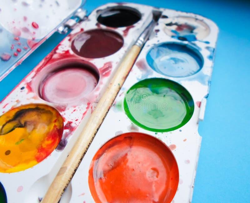 Mehrfarbige Farbe und Bürste auf blauem Hintergrund stockbilder