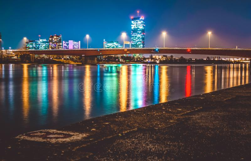 Mehrfarbige Feuer von modernen Wolkenkratzern und die Brücke in Wien glättend, werden im Fluss reflektiert Schöne Ansicht landsch lizenzfreie stockfotos