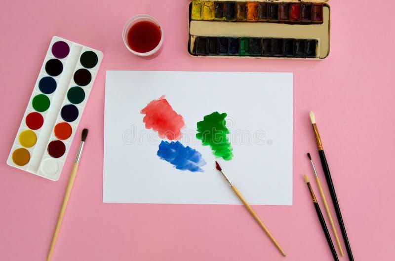 Mehrfarbige Gegenst?nde f?r das Zeichnen und Kreativit?t f?r Kinder liegt auf einem rosa Hintergrund Helle Aquarellfarben, Bleist stockfotografie