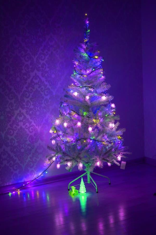 Mehrfarbige Girlande auf einem Weihnachtsbaum leuchtend mit magischem kleinem dekorativem Glasbaum mit Beleuchtung in der Dunkelh lizenzfreies stockfoto