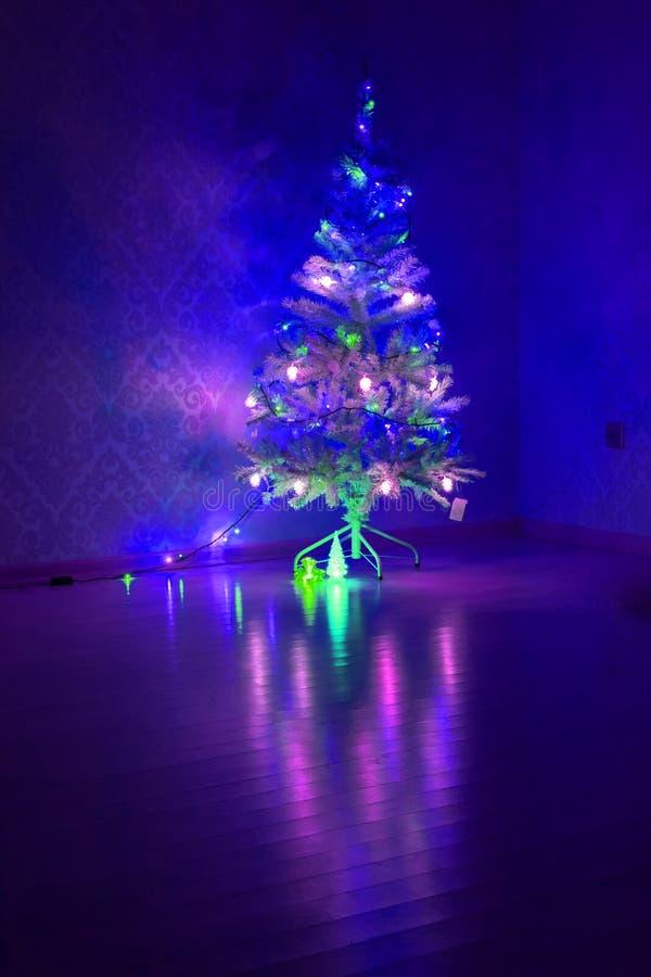 Mehrfarbige Girlande auf einem Weihnachtsbaum leuchtend mit magischem kleinem dekorativem Glasbaum mit Beleuchtung in der Dunkelh lizenzfreie stockfotos