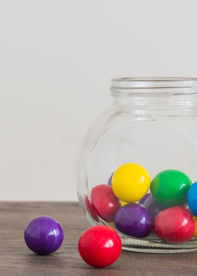 Mehrfarbige große gumballs im netten Glas und auf Holztisch lizenzfreie stockbilder