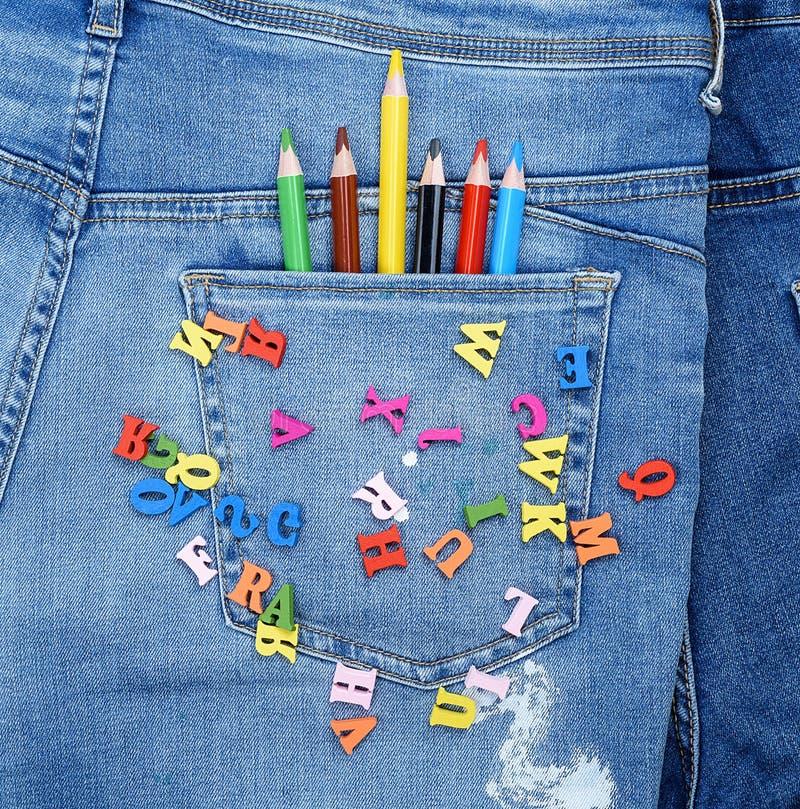 Mehrfarbige hölzerne Buchstaben des englischen Alphabetes werden auf Blue Jeans zerstreut lizenzfreie stockfotos