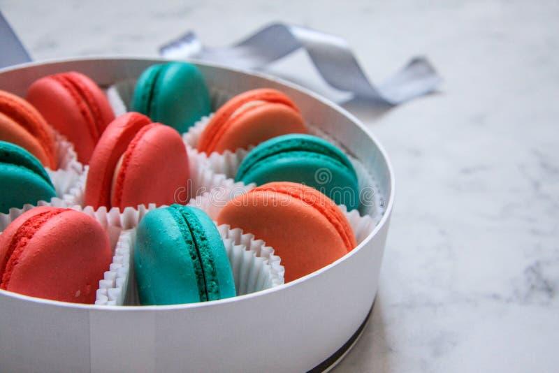 Mehrfarbige köstliche selbst gemachte macarons in einem runden weißen Kasten auf einem Marmorhintergrund lizenzfreies stockbild