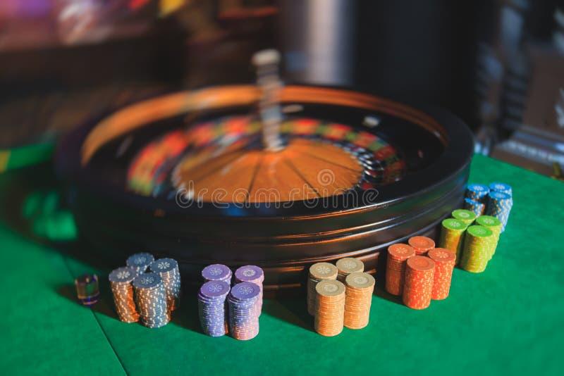 Mehrfarbige Kasinotabelle mit Rouletten in der Bewegung mit Gruppe des Spielens von reichen wohlhabenden Leuten im Hintergrund lizenzfreie stockfotografie