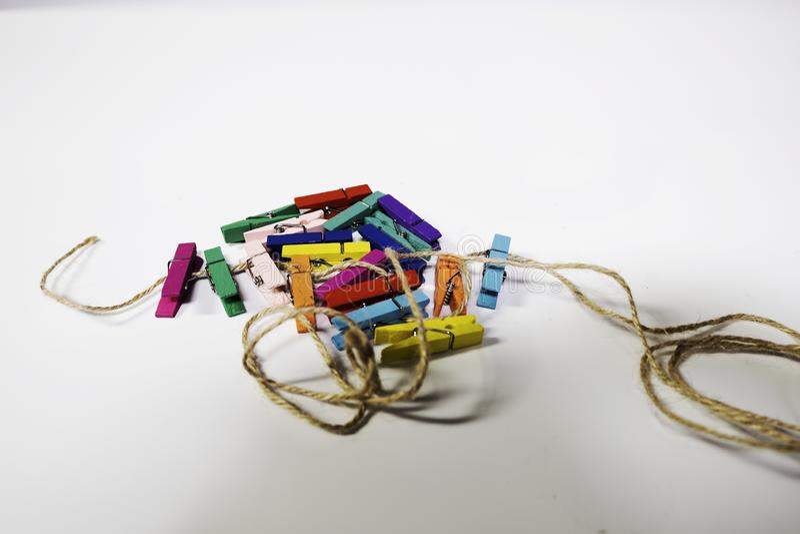 Mehrfarbige kleine Stoffklammern, zusammen stapelnd in einen Stapel und in ein Seil Der Hintergrund ist weiß stockfotos