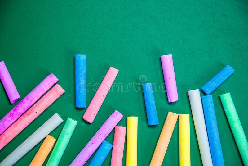 Mehrfarbige Kreiden auf einer grünen Tafel stockfoto