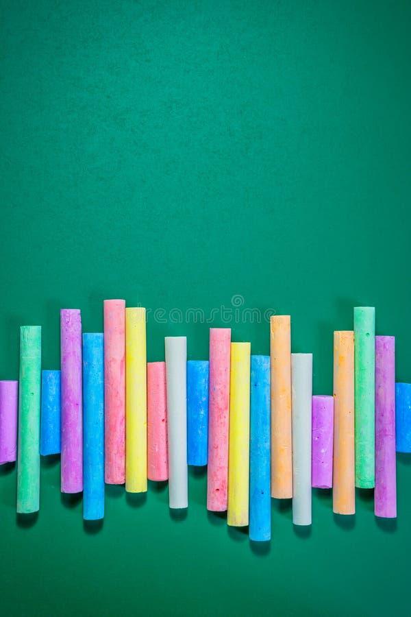 Mehrfarbige Kreiden auf einer grünen Tafel lizenzfreie stockfotografie