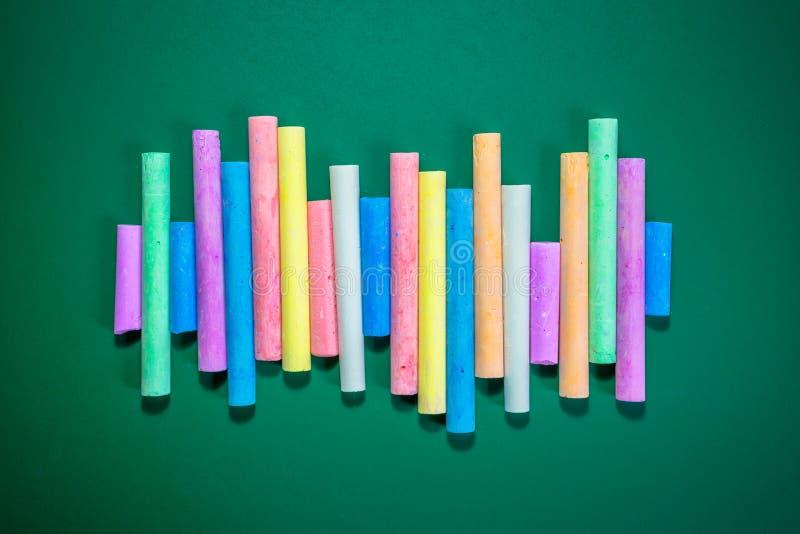 Mehrfarbige Kreiden auf einer grünen Tafel stockbilder