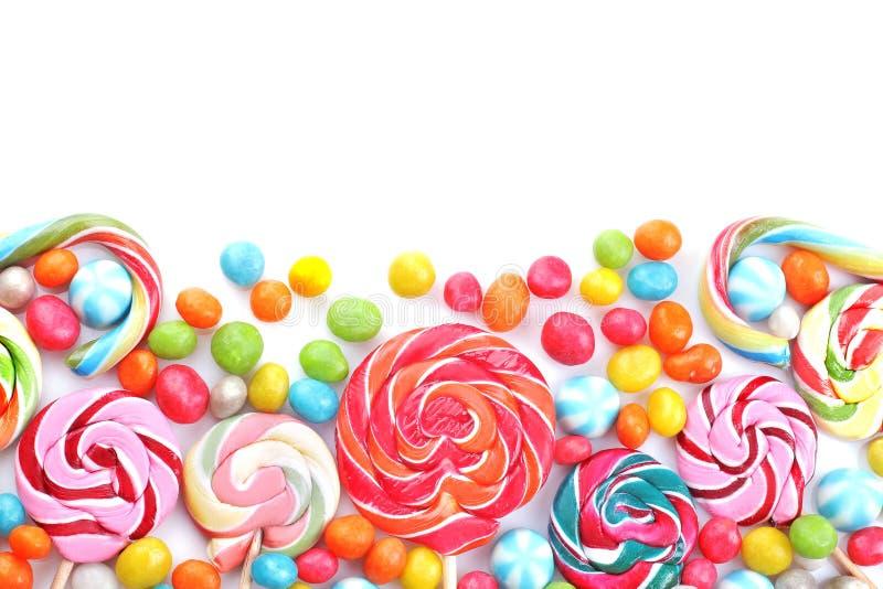 Mehrfarbige Lutscher und runde Süßigkeiten auf einem weißen Hintergrund lizenzfreie stockfotos