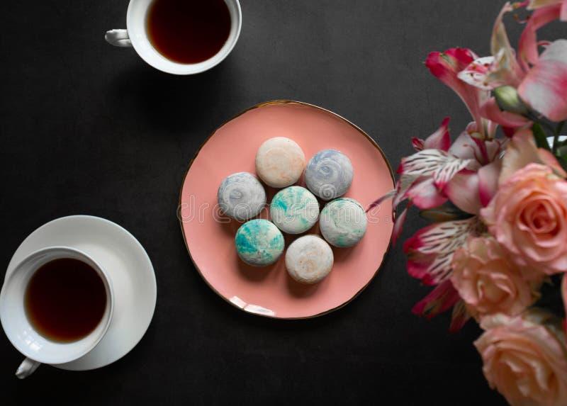 Mehrfarbige macarons auf der rosa Platte auf einer dunklen Tabelle weiße Tasse Tee oder Kaffee Frühstück mit Nachtisch Blumenstra lizenzfreies stockbild