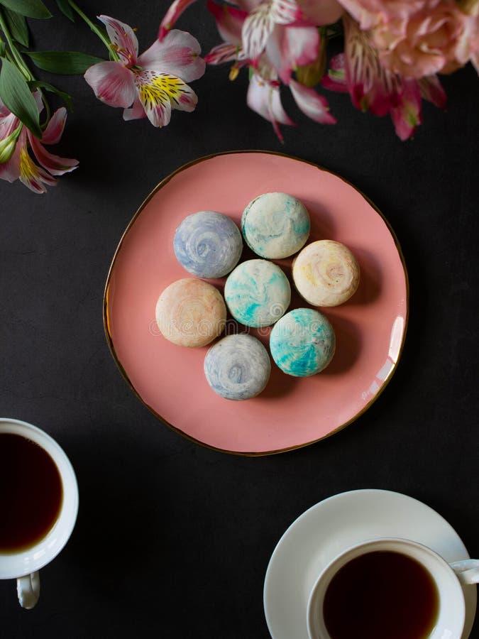Mehrfarbige macarons auf der rosa Platte auf einer dunklen Tabelle weiße Tasse Tee oder Kaffee Frühstück mit Nachtisch Blumenstra lizenzfreie stockbilder