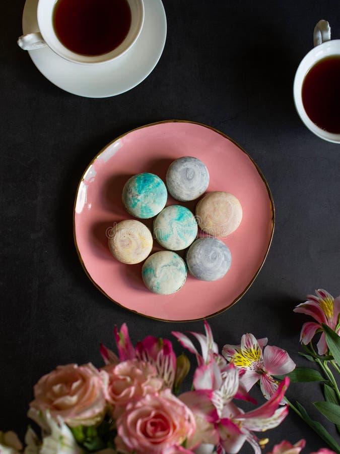Mehrfarbige macarons auf der rosa Platte auf einer dunklen Tabelle weiße Tasse Tee oder Kaffee Frühstück mit Nachtisch Blumenstra stockfotografie