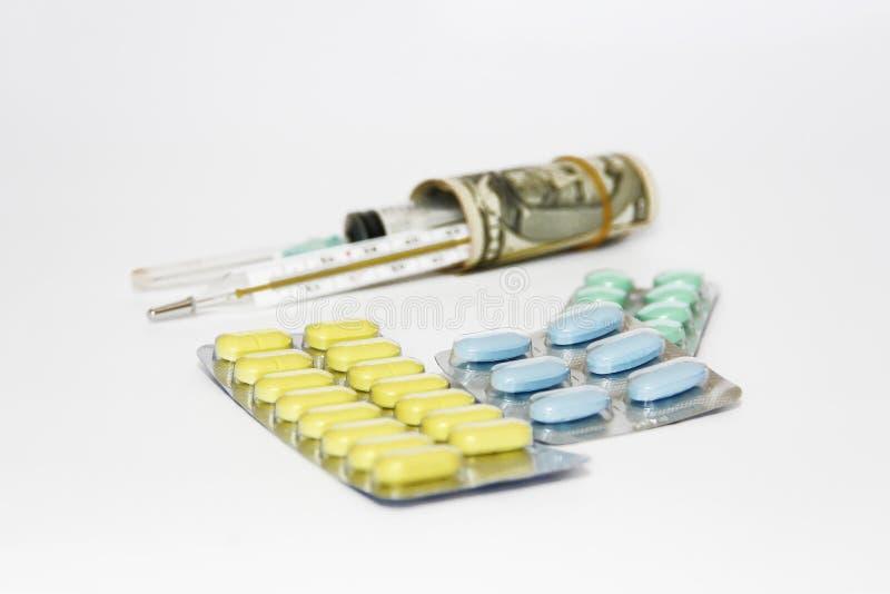 Mehrfarbige medizinische Pillen, Thermometer, Spritze und Dollar lizenzfreies stockbild