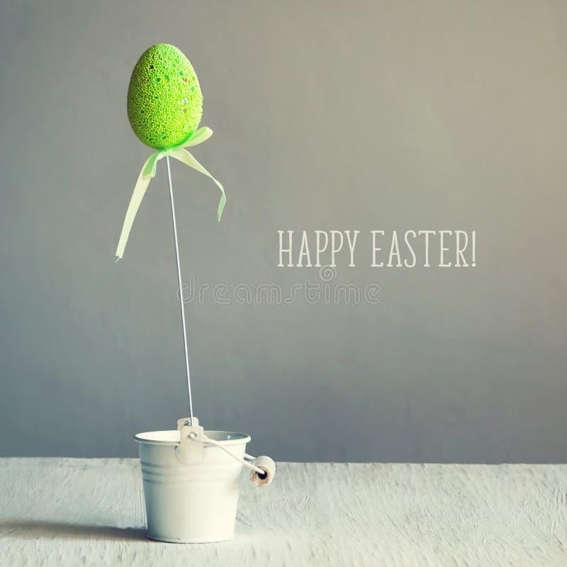 Mehrfarbige Ostereier auf Stöcken im kleinen weißen Eimer Die Aufschrift von fröhlichen Ostern Kopieren Sie Platz stockfoto