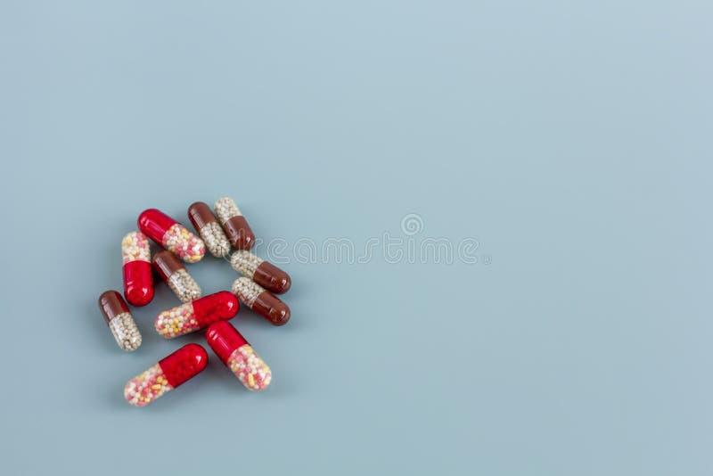 Mehrfarbige Pillen oder Kapseln auf einem blauen Hintergrund mit Kopienraum stockbild