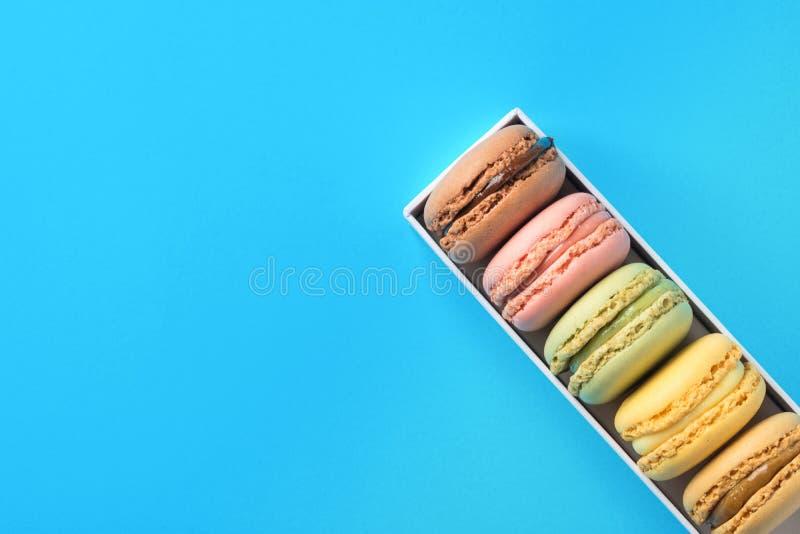 Mehrfarbige rosa grüne gelbes Brown-Mokka-Makronen in der Geschenkbox auf Blau Bäckerei-Süßigkeiten-Konditorei-Plakat lizenzfreies stockbild