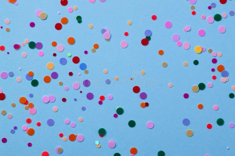 Mehrfarbige runde Paillette auf einem blauen Hintergrund mit Konfettis stockbilder