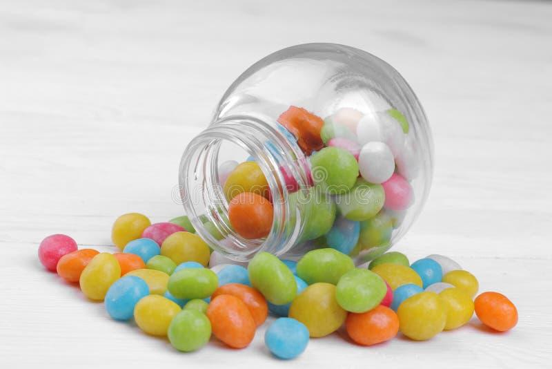 Mehrfarbige runde Süßigkeit in einem Glasgefäß auf einem weißen Hintergrund lizenzfreies stockbild