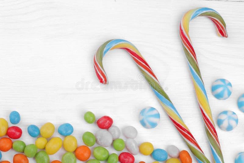 Mehrfarbige runde Süßigkeit und bunte Lutscher auf einem weißen hölzernen Hintergrund lizenzfreie stockfotografie