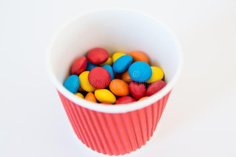 Mehrfarbige runde Süßigkeitsdragéelüge in einem roten Papierglas stockfoto