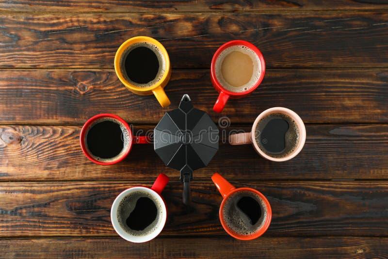 Mehrfarbige Schalen und Kaffeemaschine auf h?lzernem Hintergrund, Draufsicht stockfoto