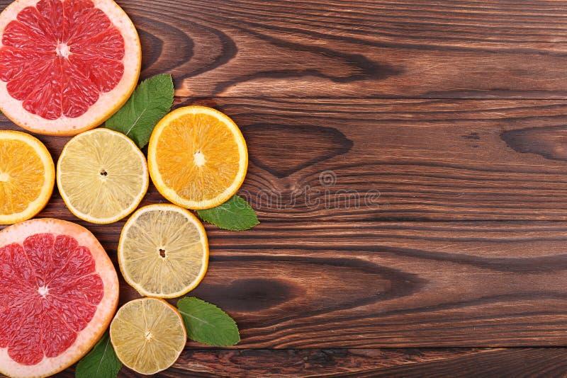 Mehrfarbige Scheiben der saftigen orange, reifen Zitrone und der frischen Pampelmuse mit hellgrünen Blättern auf einem dunkelbrau lizenzfreies stockbild