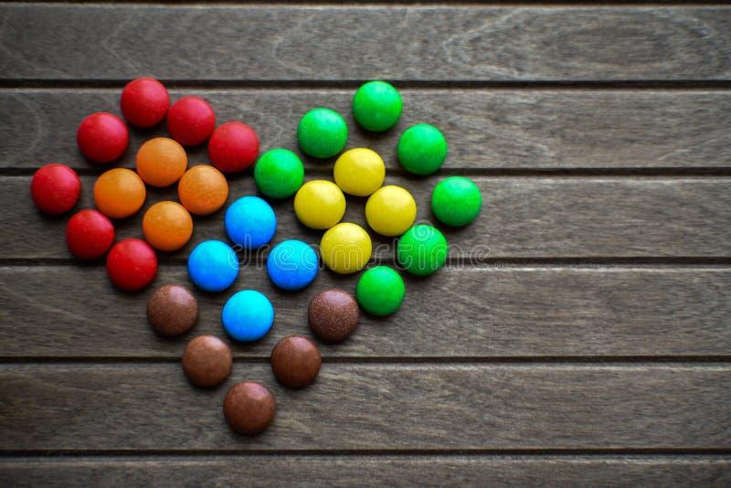 Mehrfarbige Schokoladendragées werden in Form eines Herzens ausgebreitet die Farben der LGBT-Flagge lizenzfreies stockfoto