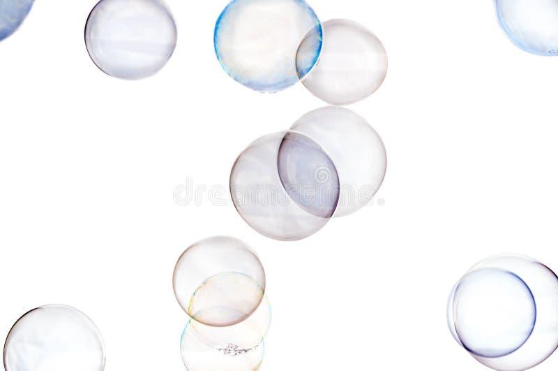 Mehrfarbige Seifenblasen schließen oben auf einem weißen Hintergrund stockfotos
