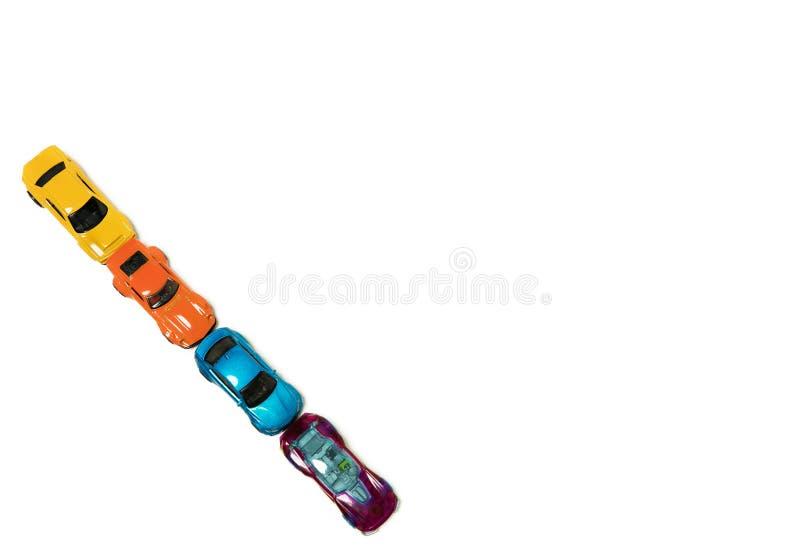 Mehrfarbige Spielzeugautos werden auf einem weißen Hintergrund ausgerichtet Kopieren Sie Raum f?r Text stockfoto