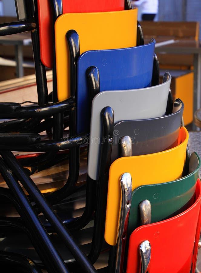 Mehrfarbige Stühle häuften oben vor einem Restaurant an stockfotos