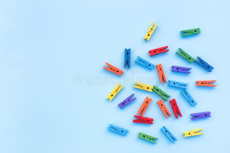 Mehrfarbige Wäscheklammern auf einem blauen Hintergrund stockbild