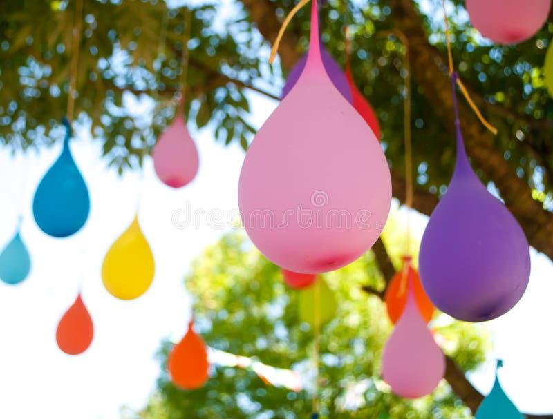 Mehrfarbiger Ballon gefüllt mit Wasser, hängend an einem Baum lizenzfreie stockfotos