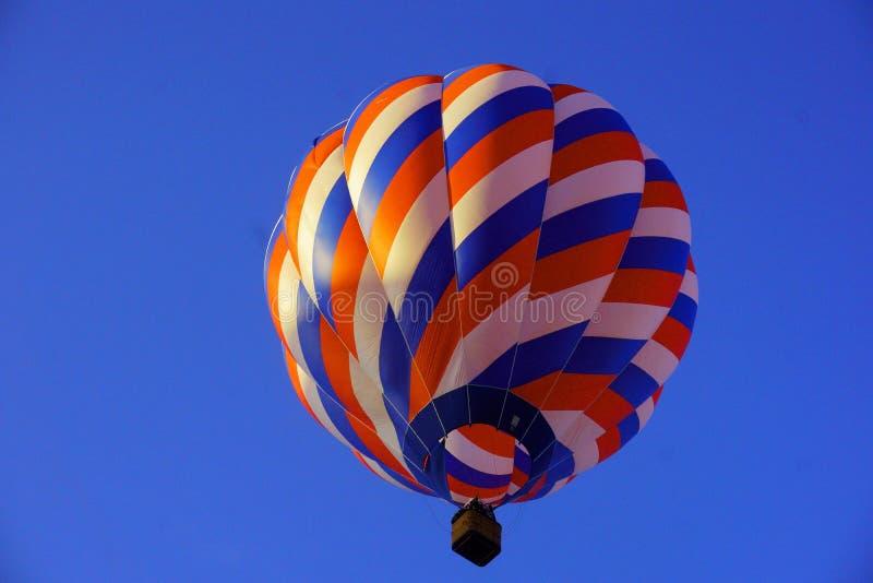 Mehrfarbiger Heißluftballon im Flug am Abend mit tiefem Hintergrund des blauen Himmels lizenzfreie stockfotos