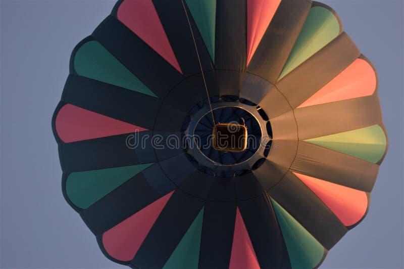 Mehrfarbiger Heißluftballon im Flug am Abend mit tiefem Hintergrund des blauen Himmels lizenzfreies stockbild