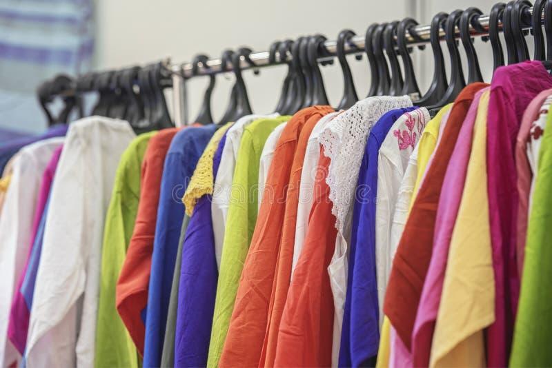 Mehrfarbiger Jugendsommerkittel auf einem Aufhänger Bunte Kleidung auf Aufhängern für Verkauf im Geschäft Sommersaison, Zusammens lizenzfreies stockbild