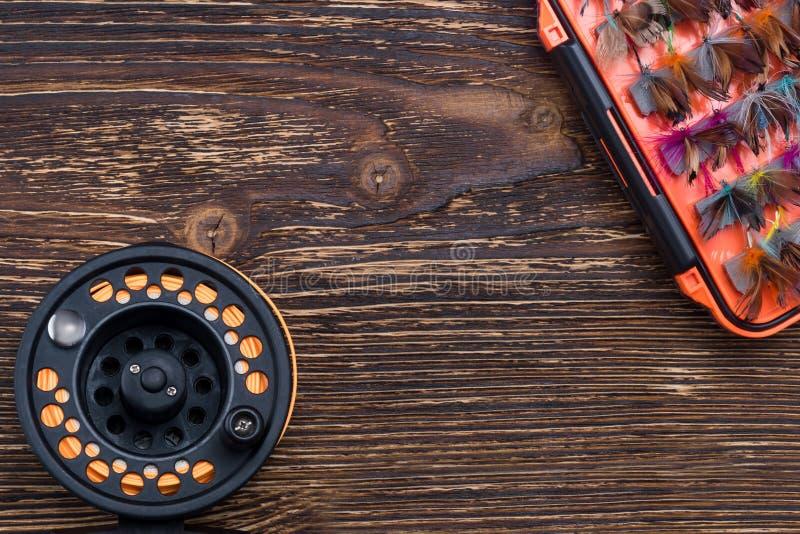 Mehrfarbiger Köder für die Fischerei in einem Kasten und eine Spule für Angeln auf einem hölzernen Hintergrund lizenzfreie stockfotos