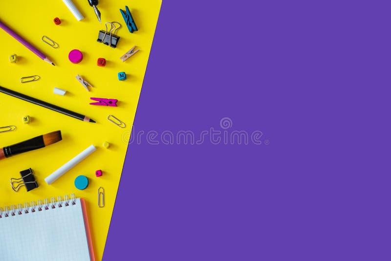 Mehrfarbiger Schulbedarf auf weißem und gelbem Hintergrund mit Kopienraum lizenzfreies stockbild