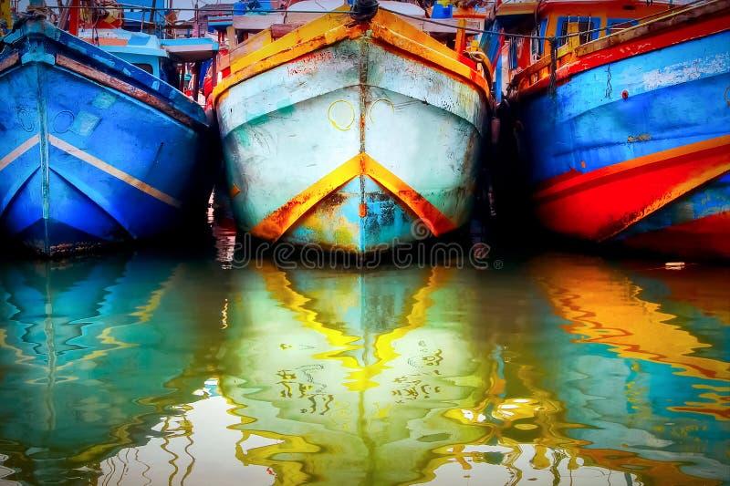 Mehrfarbiges altes Boot im Fischereihafen Farbige Reflexionen im Wasser Sri Lanka Tangalle lizenzfreies stockbild