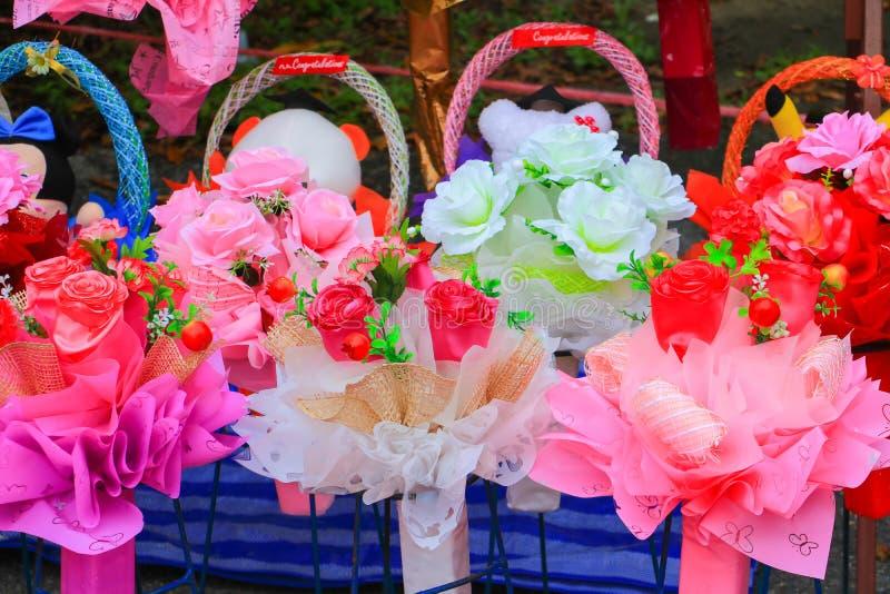 Mehrfarbiges Plastikkünstliches der bunten Rosenblume für schönen Hintergrund stockfotografie