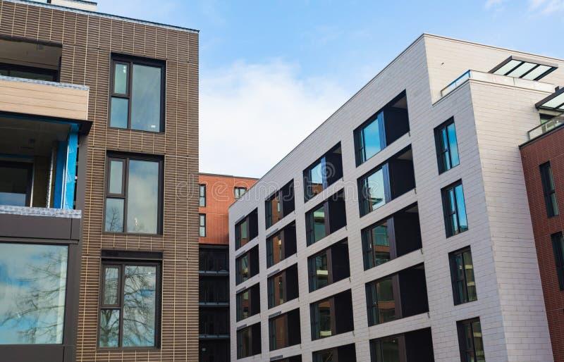 Mehrstöckige moderne Hausnahaufnahme Maurerarbeit, Fenster, Reflexionen des Himmels im Glas Tageszeit, Sonne Moderner Appartement lizenzfreies stockfoto