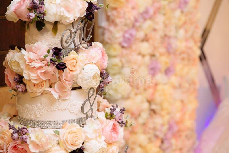 Mehrstufige Hochzeitstorte der Nahaufnahme verziert mit Blumenständen auf einer Tabelle Konzept des Essens, der Bonbons und der N stockfotos