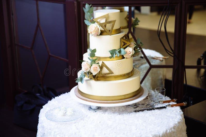 Mehrstufige Hochzeitstorte verziert mit Blumenständen auf einer Tabelle Konzept des Essens, der Bonbons und der Nachtische an ein stockfotos