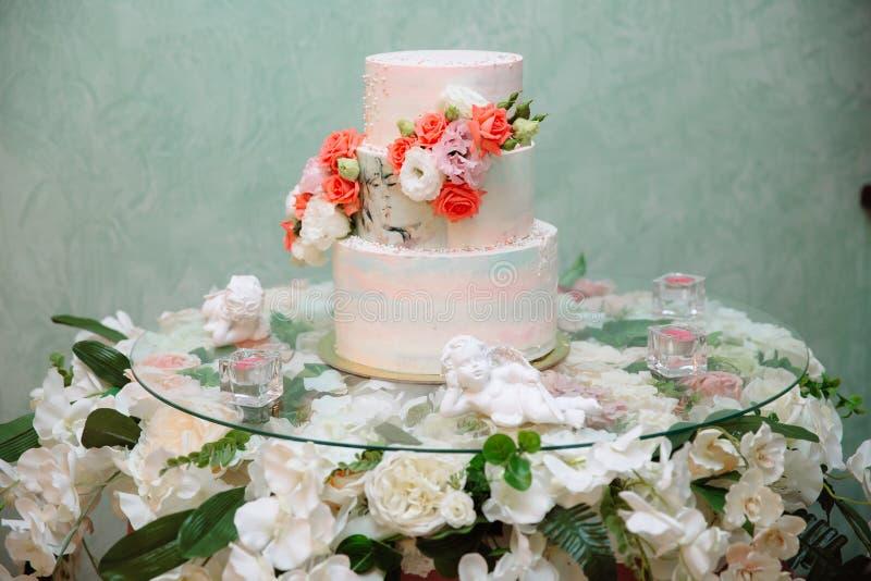 Mehrstufige Hochzeitstorte verziert mit Blumenständen auf einer Tabelle Konzept des Essens, der Bonbons und der Nachtische an ein stockfoto