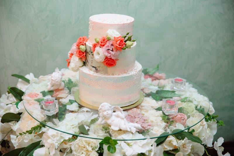 Mehrstufige Hochzeitstorte verziert mit Blumenständen auf einer Tabelle Konzept des Essens, der Bonbons und der Nachtische an ein stockfotografie