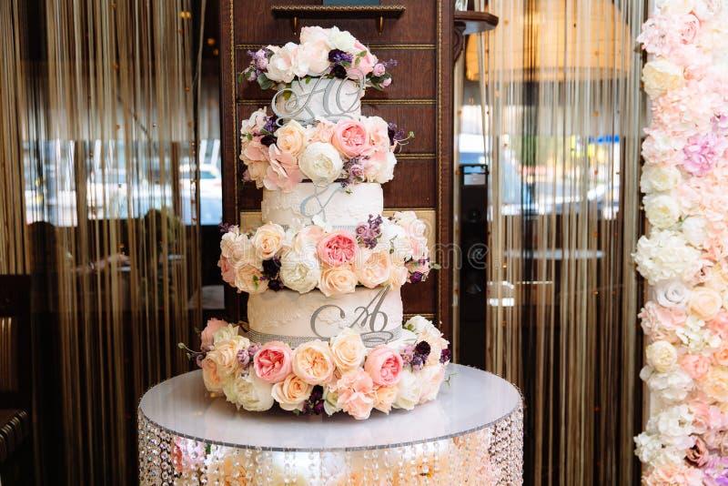 Mehrstufige Hochzeitstorte verziert mit Blumenständen auf einer Tabelle Konzept des Essens, der Bonbons und der Nachtische an ein lizenzfreie stockbilder