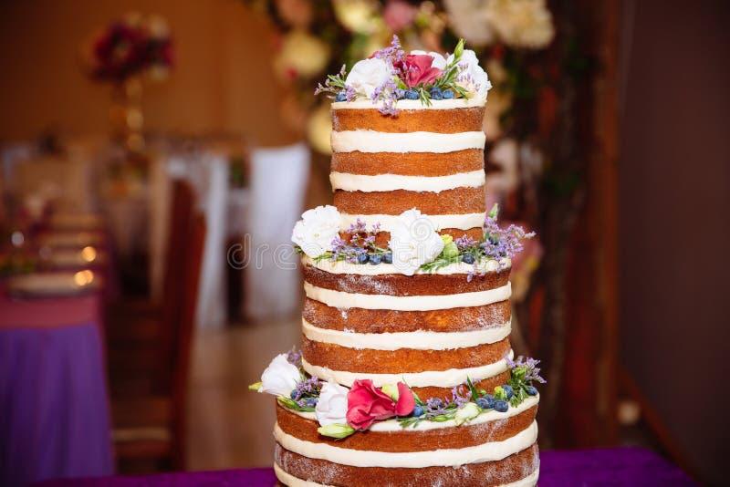 Mehrstufige weiße Hochzeitstorte verziert mit Blumenständen auf einer Tabelle Konzept des Essens, der Bonbons und der Nachtische  stockfotografie