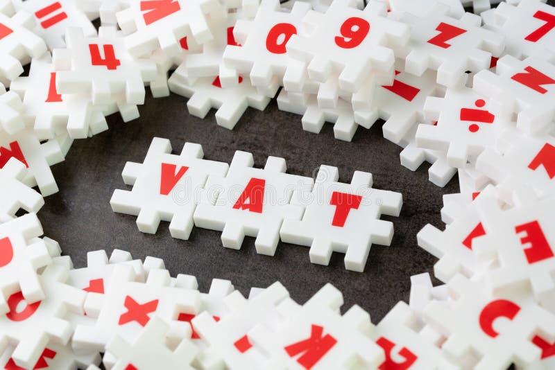 Mehrwertsteuer, Mehrwertsteuer-Konzept, weiße Puzzlespiellaubsäge mit dem Alphabet, welches das Wort Mehrwertsteuer in der Mitte  lizenzfreie stockfotografie